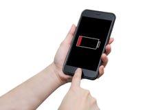 Mano usando el teléfono elegante con la advertencia baja de la muestra de la batería en el disp Fotografía de archivo libre de regalías