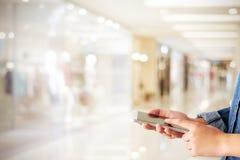 Mano usando el teléfono elegante sobre tienda de la falta de definición con backgrou de la luz del bokeh Foto de archivo
