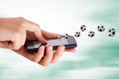 Mano usando el teléfono elegante con el tema del fútbol Fotos de archivo libres de regalías