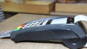 Mano usando el terminal del banco para el pago con tarjeta de crédito almacen de video