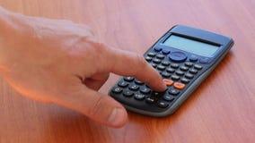 Mano usando la calculadora almacen de metraje de vídeo