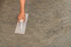 Mano usando la paleta de acero para acabar la superficie concreta mojada pulida imagen de archivo libre de regalías