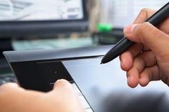 Mano usando la tablilla digital de la pluma Foto de archivo libre de regalías