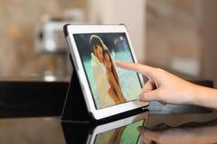Mano usando las fotos de observación de una tableta en casa Imágenes de archivo libres de regalías