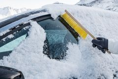 Mano usando nieve arrebatadora del cepillo en el parabrisas del coche Foto de archivo
