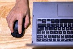 Mano usando ratón y el ordenador portátil del ordenador en el escritorio foto de archivo