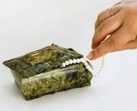Mano verde del cofanetto gli che cattura la collana della perla Immagine Stock