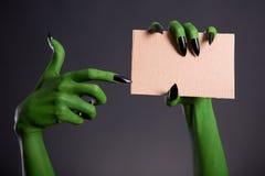 Mano verde del monstruo con los clavos negros que señalan en el pedazo en blanco de c Fotografía de archivo