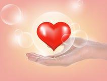 Mano y corazón de la mujer; burbujas en fondo Fotos de archivo libres de regalías