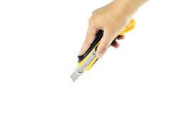 Mano y cortador amarillo en el fondo blanco Fotos de archivo libres de regalías