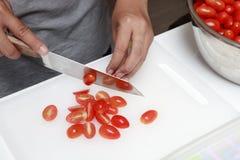 Mano y cuchillos que rebanan el tomate rojo Foto de archivo libre de regalías