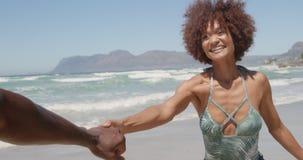 Mano y funcionamiento del hombre de la tenencia de la mujer en la playa en la sol 4k metrajes