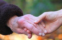 Mano y mano amiga de la mujer mayor Imagen de archivo