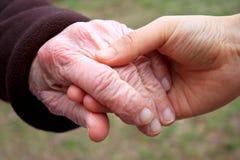 Mano y mano amiga de la mujer mayor Imagen de archivo libre de regalías