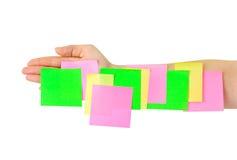 Mano y papel de nota multicolor Imagen de archivo