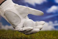 Mano y pelota de golf Imagenes de archivo