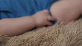 Mano y piernas preciosas del bebé la pequeñas se cierran para arriba en cama almacen de video