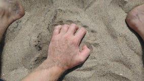 Mano y pies en arena en el día soleado de la playa foto de archivo