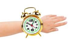 Mano y reloj de alarma como un reloj Imagen de archivo