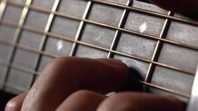 Mano y secuencias masculinas en fretboard Funcionamiento de la música vídeo de la macro 4K metrajes