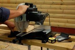 Mano y sierra del carpintero imagenes de archivo