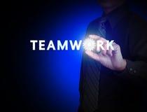 Mano y trabajo en equipo de la palabra con el engranaje Foto de archivo
