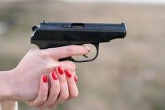 Mano y un arma de la mujer Foto de archivo