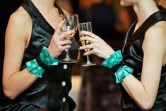 Mano y vidrio de la huésped con el vino en el partido imágenes de archivo libres de regalías