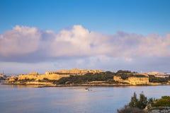 Manoel Island en la salida del sol con el barco de pesca y las nubes hermosas Imagen de archivo