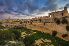 Manoel Island, Malta - Abandoned limestone fortress at the center of Manoel Island with Saint Paul`s Cathedral. And Valletta at the background Royalty Free Stock Photo