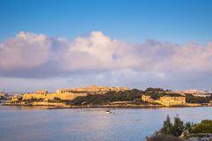 Manoel Island at sunrise with fishing boat and beautiful clouds. Malta, Sliema Stock Image