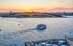 The Manoel Port on sunset, Valletta, Malta. Valletta walls are perfect viewpoint to enjoy the fiery sunset over the Manoel Port and watch the ferries between Royalty Free Stock Photo