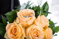 Manojo anaranjado de las rosas con los anillos de bodas Foto de archivo