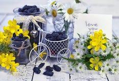 Manojo con los wildflowers, la baya azul en tarros lindos y la pequeña bicicleta Imágenes de archivo libres de regalías