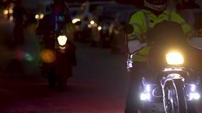 Manojo de amigos del motorbiker que conducen lentamente la calle oscura con las linternas brillantes almacen de video