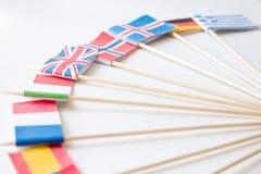 Manojo de banderas de papel miniatura de varios países: Grecia, Alemania, Suecia, Noruega, Inglaterra, Italia, Francia, España fotos de archivo libres de regalías