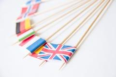 Manojo de banderas de papel miniatura de varios países: Reino Unido, Alemania, Suecia, Noruega, Italia, Francia, España imagenes de archivo