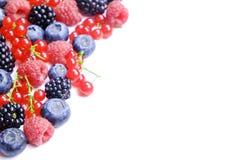 Manojo de bayas mezcladas en pila de la cosecha en el fondo blanco Composición colorida con la fresa orgánica fresca, arándano, b imagenes de archivo