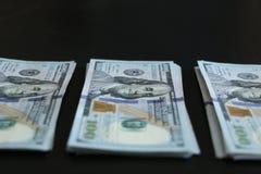 Manojo de 100 billetes de dólar en fondo negro Foto de archivo
