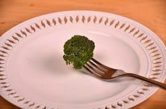 Manojo de bróculi verde fresco en la placa blanca sobre fondo de madera Foto de archivo libre de regalías