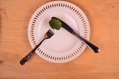 Manojo de bróculi verde fresco en la placa blanca sobre fondo de madera Fotografía de archivo libre de regalías