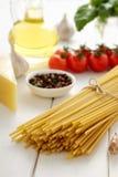 Manojo de bucatini crudo con los tomates, el ajo, la albahaca y el queso frescos en la tabla de madera blanca Fotos de archivo libres de regalías