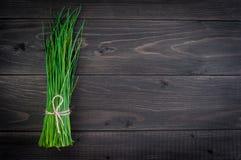 Manojo de cebolletas frescas en una tabla de cortar de madera, foco selectivo Fotos de archivo