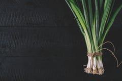 Manojo de cebolletas jovenes verdes con las raíces en un fondo oscuro negro de la opinión superior del viejo vintage de los table foto de archivo libre de regalías