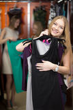 Manojo de compra sonriente de la mujer de ropa en tienda Imagenes de archivo