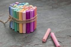 Manojo de creyones en colores pastel coloreados con los creyones color de rosa a un lado en fondo oscuro fotografía de archivo