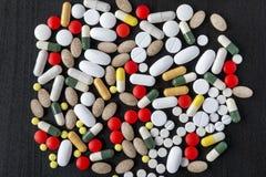 Manojo de diversas píldoras del color en fondo negro Fotografía de archivo libre de regalías