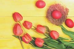 Manojo de flores cerca de los huevos de Pascua rosados en jerarquía del heno Imágenes de archivo libres de regalías