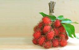 Manojo de frutas frescas maduras del Rambutan en la tabla de madera, con el espacio libre para el texto Fotografía de archivo libre de regalías