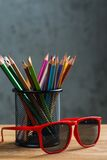 Manojo de lápices del color y de gafas de sol rojas en un soporte Fotos de archivo